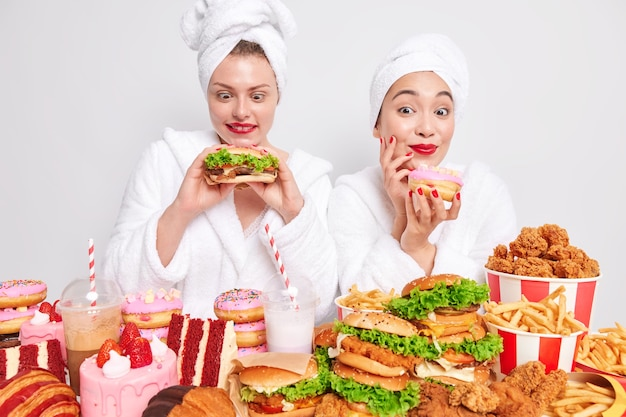 Horizontal shot of happy women enjoy domestic party hold hamburger and doughnut efford to eat junk food