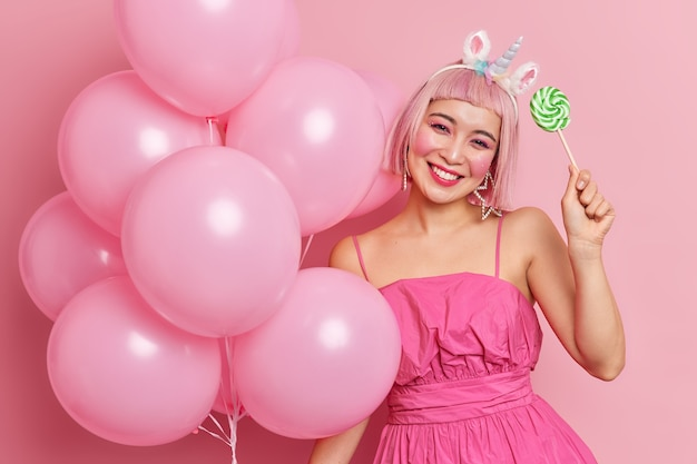 Horizontal shot of happy young asian woman celebrates birthday holds inflated balloons makes decorations for party holds sweet lollipop wears fashionable dress