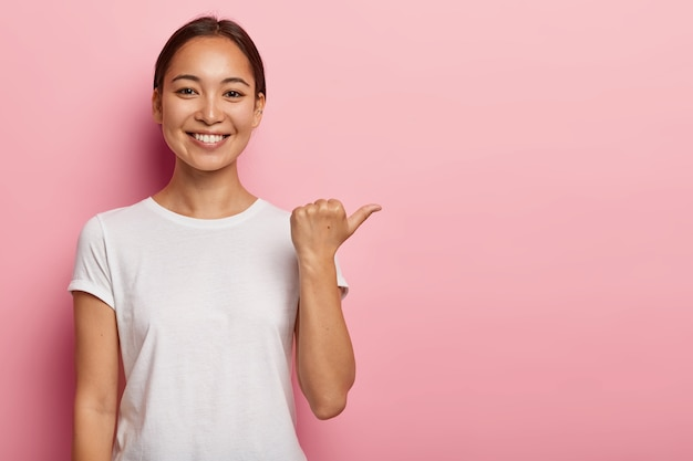 Horizontal shot of happy young asian woman points away on copy space, demonstrates something good, wears white t shirt, helps pick best choice, recommends product, models over pink wall