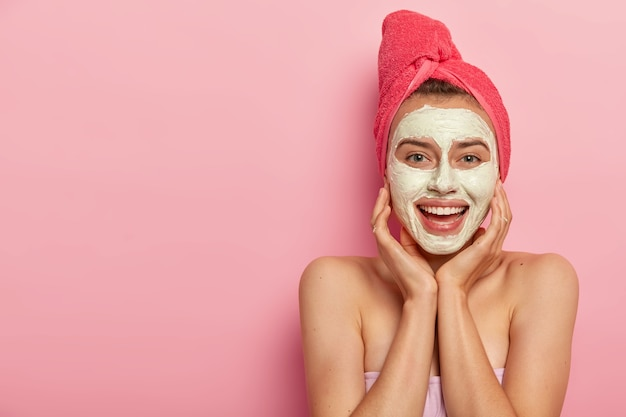Horizontal shot of happy young european lady applies facial mud mask, touches cheeks, avoids irritation of skin, has naked shoulders