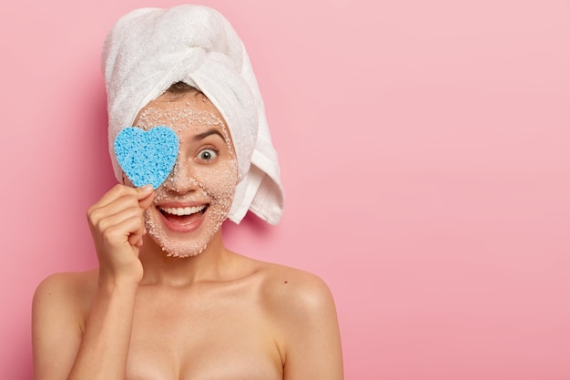 Colpo orizzontale di felice giovane modello femminile copre gli occhi con una spugna cosmetica, pulisce il viso con una maschera scrub al sale marino bianco naturale, visita il salone spa, ha una pelle sana lenitiva, corpo nudo, modelli al coperto