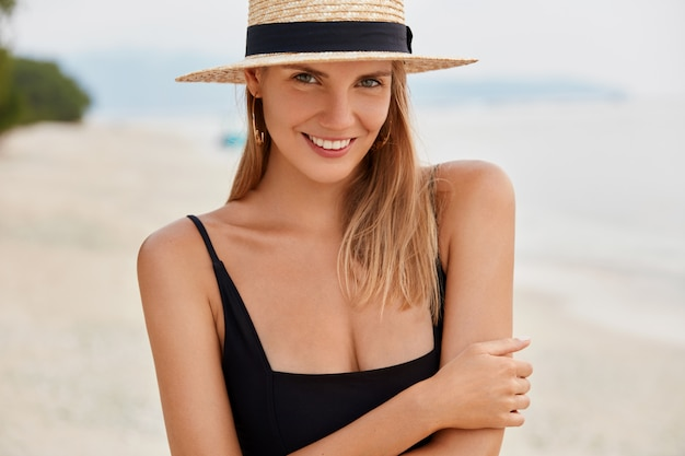 Horizontal shot of happy young female model with pleased expression, warm smile, wears straw hat and bathing suit.
