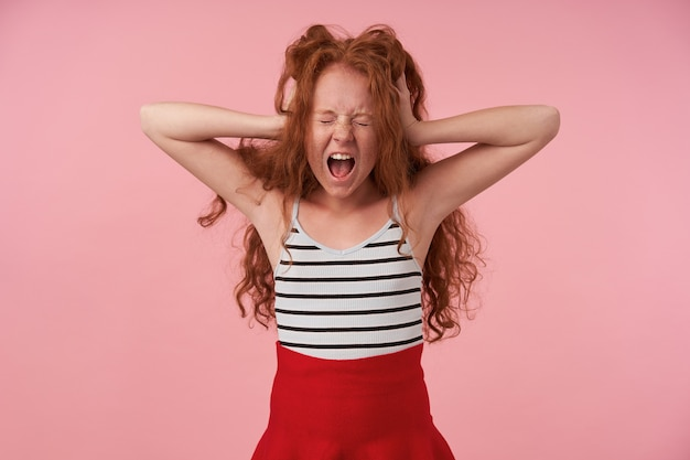 Horizontal shot of haywire long haired curly girl in red skirt and striped top holding head with raised palms, screaming loud with closed eyes, isolated over pink background