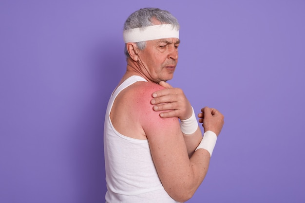 Horizontal shot of injured senior man posing sideways, mature male with white head band, elderly sportrsman
