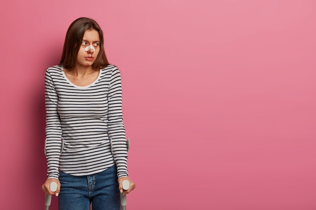 Inquadratura orizzontale di una donna ferita che ha avuto un incidente d'auto, si riprende a casa, ha un grave trauma, guarda da parte, indossa un cerotto medico sul naso rotto, isolato sul muro rosa. disabilità, concetto di cure mediche