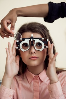 Horizontal shot of interested and curious caucasian girl on appointment with eye care specialist wearing phoropter while ophthalmologist checking her vision, sitting over yellow wall