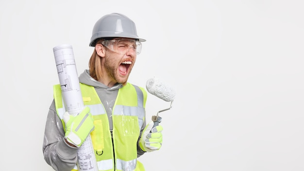 Horizontal shot of irritated male construction worker exclaims negatively holds blueprint and painting roller