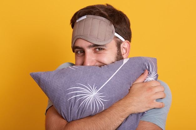 Horizontal shot of joyful man hugging his pillow with pleasant facial expression isolated over yellow background, male with blindfold on forehead, feels happy, wants to sleep long hours during weekend