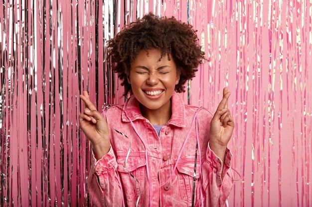 Horizontal shot of joyful overjoyed female with afro hairstyle, crosses fingers, hopes for fortune, wears pink jacket, has eyes shut