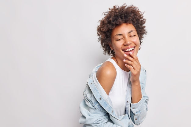 Horizontal shot of joyful overjoyed woman with curly hair smiles broadly feels very happy and upbeat expresses authentic positive emotions keeps eyes closed wears denim jacket white t shirt