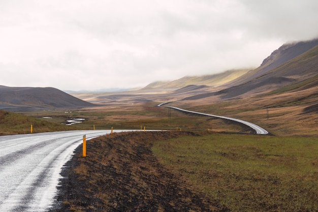 Horizontal shot of a landscape in iceland with a long asphalt road