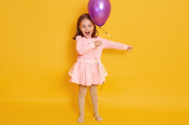 Horizontal shot of little girl with purple balloon isolated over yellow all female child shouting somethig, celebrating herbirtday, kid wearing rosy dress and having dark hair.