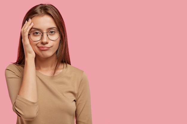 Horizontal shot of lovely female has bored displeased facial expression, looks in discontent, wears round spectacles and casual sweater, isolated over pink wall with blank copy space aside