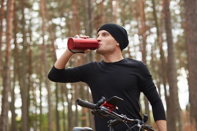 Horizontal shot of man riding mountain bike in forest