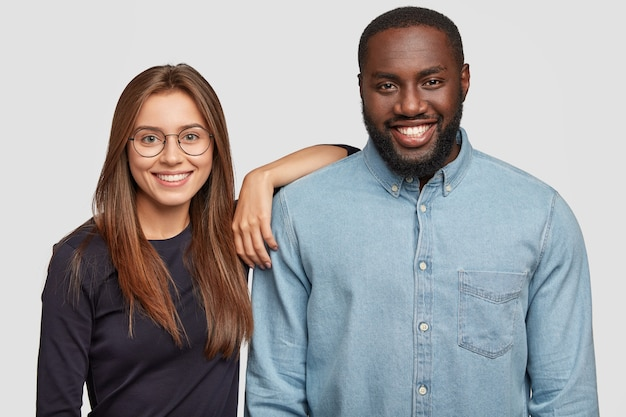 Horizontal shot of mixed race couple stand closely to each other, being in good mood