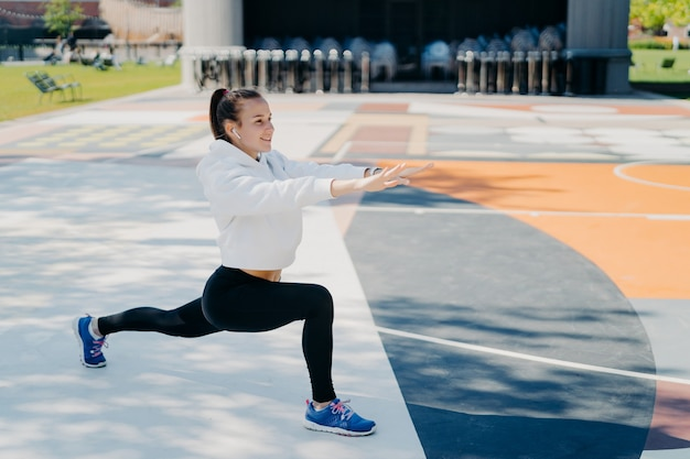 Horizontal shot of motivated sporty woman stretches legs and arms does warming up exercises before workout looks forward dressed in sportsclothes poses outside on big stadium. exercising concept