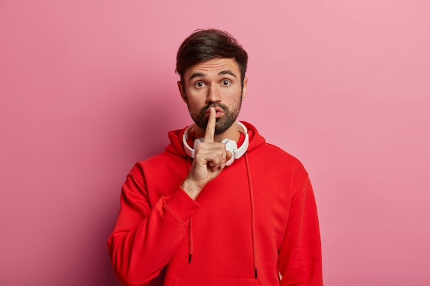Horizontal shot of mysterious bearded man makes shush gesture, shows hush sign, asks not tell secret, presses index finger to lips, wears red sweater, poses over rosy pastel wall. secrecy concept