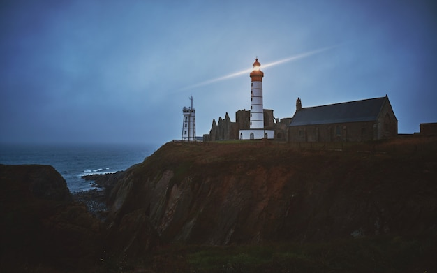 Horizontal shot of a mysterious town on a cliff with a white turned-on lighthouse during dusk