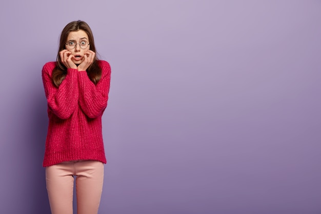 Horizontal shot of nervous stressed woman feels neurotic, bites finger nails, wears oversized long red jumper, reacts on astonishing news, stands over purple wall empty space for information