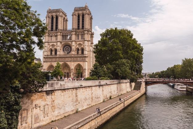 Horizontal shot of notre dame cathedral by the bridge before it burned down, full of people walking