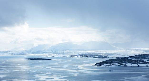 Горизонтальный снимок водоема, покрытого льдом, в окружении гор под белыми облаками