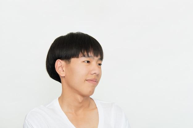 Горизонтальный снимок красивого молодого парня с позитивным выражением карих глаз, которого кто-то хвалит, небрежно одетого, изолированной белой стены