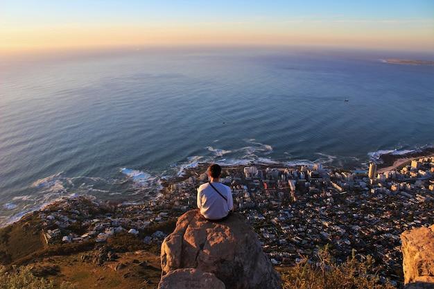 바위 가장자리에 앉아 해안선 도시를 바라 보는 남자의 수평 샷