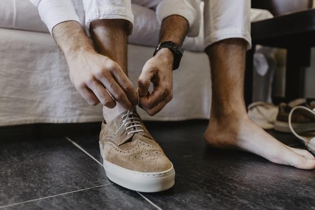 갈색 신발 끈을 묶는 남자의 수평 샷