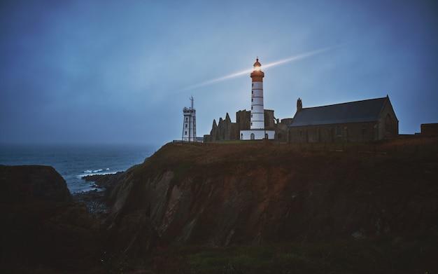 Горизонтальная съемка таинственного города на скале с белым включенным маяком во время заката
