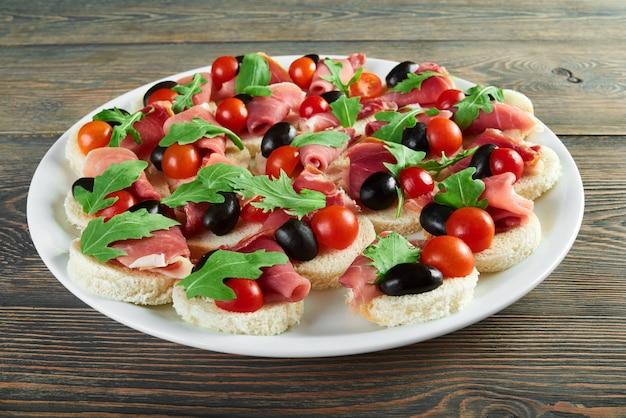 Горизонтальный снимок тарелки с канапе с ветчиной, помидорами черри и черными оливками, украшенными рукколой, рукколи, съедобными овощами, беконом, хамоном, закусками, меню ресторана.