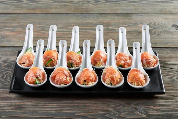 サーモンとチーズのプレートの水平方向のショットは、大部分のスプーンで繊細な美味しい前菜を食べるレストランカフェ高級ライフスタイルの魚の燻製コンセプトを提供しています。