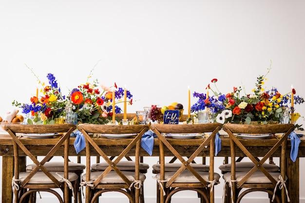 화려한 꽃과 촛불로 장식 된 나무 의자가있는 테이블의 가로 샷