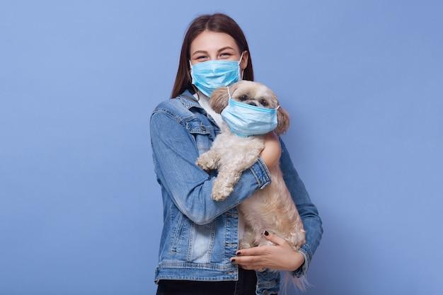 医療保護フェイスマスク、ライラックの壁に分離されたポーズの手でマスクを持つ女性持株犬を身に着けている大人の女性の水平ショット。コロナウイルス、covid 19、病気、パンデミックのコンセプト。
