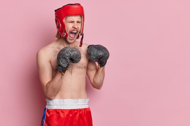 Горизонтальный снимок разгневанного боксера, громко кричащего, тренируется в тренажерном зале, готовится к спортивному турниру