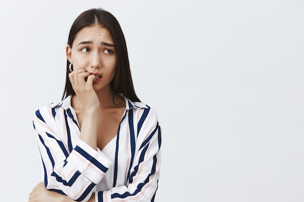 Горизонтальный снимок встревоженной симпатичной студентки в полосатой блузке, нервно кусающей ноготь, хмурящейся и смотрящей в сторону, опасающейся последствий, стоящей над серой стеной