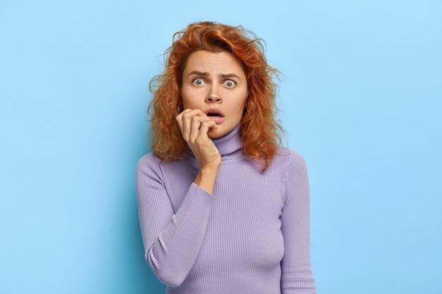 Горизонтальный снимок встревоженной испуганной женщины открывает рот, чувствует себя напряженным и нервным