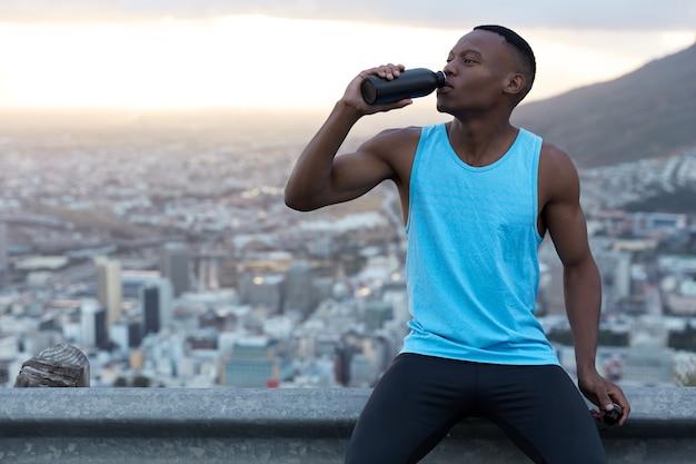 筋肉質の手で魅力的なアクティブな若い男性の水平方向のショット、水のボトルを保持し、激しいジョギングの後に休む、スポーツ服を着て、道路標識に座っている