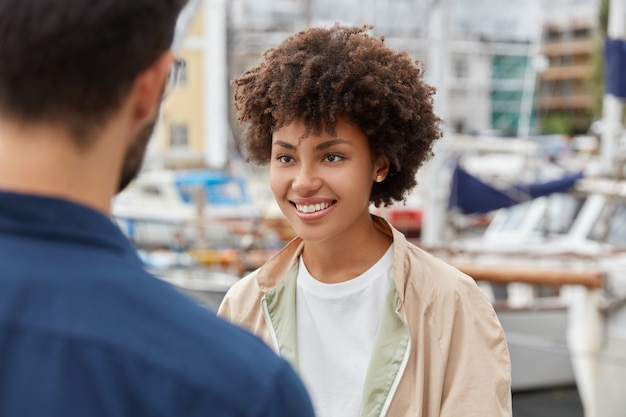 魅力的なアフリカ系アメリカ人の女の子の水平方向のショットは、心地よい外観、歯を見せる笑顔を持っています