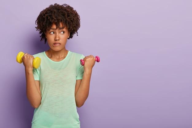 Горизонтальный снимок привлекательной кудрявой женщины, которая кусает нижнюю губу, поднимает гантели, работает над бицепсами, носит повседневную футболку, сосредоточена в стороне