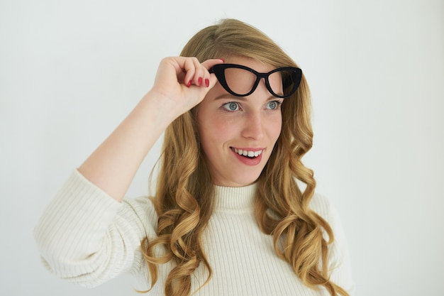 Горизонтальный снимок привлекательной молодой девушки в белой водолазке, взволнованно улыбающейся, поднимающей свои стильные очки «кошачий глаз» и смотрящей вперед с удивлением, потрясенной некоторыми неожиданными новостями