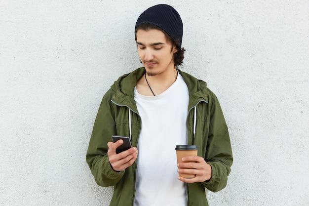 세련된 헤드 기어와 녹색 재킷에 매력적인 younsgter의 가로 샷, 한 손에 현대 스마트 폰을 보유하고