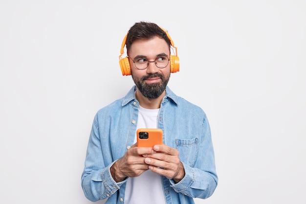 수염 난 만족 한 수염 난 남자의 수평 샷은 재생 목록에서 음악을 선택합니다. 데님 셔츠를 입은 스마트 폰과 헤드폰을 보유하고 있습니다.