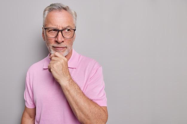 あごひげを生やした思いやりのある男の水平方向のショットは、しんみりと見えるあごを保持します