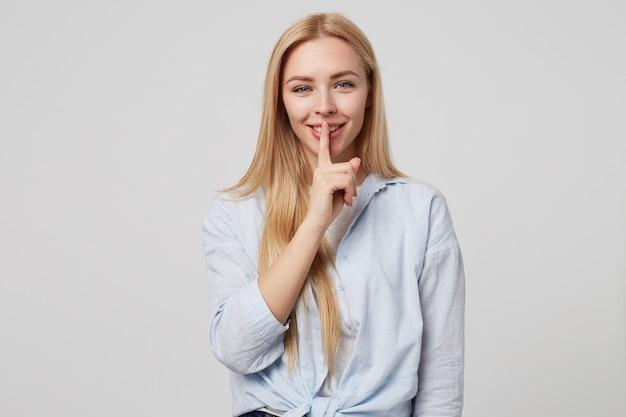 Горизонтальный снимок красивой блондинки с длинными волосами, держащей палец на улыбающихся губах, демонстрирующей знак молчания, стоя