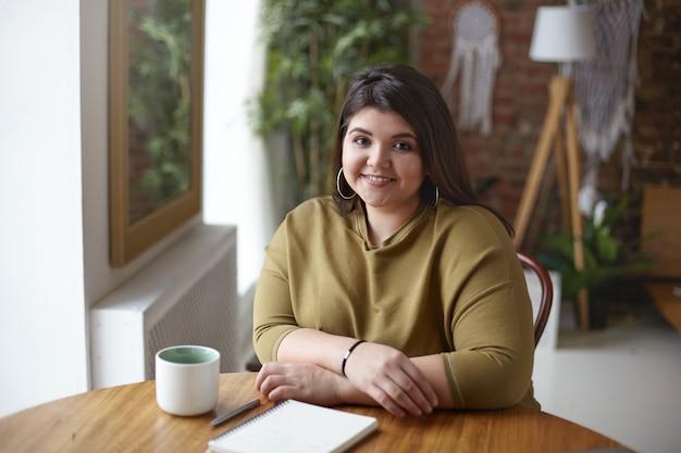 Горизонтальный снимок красивой дружелюбной молодой европейской женщины с лишним весом, которая пьет кофе в уютном кафетерии, записывает идеи или делает зарисовки, сидя за деревянным столом с дневником и кружкой