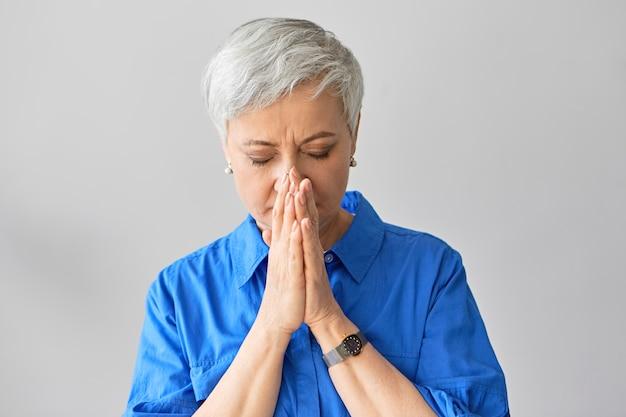 青いシャツを着た美しい白髪のスタイリッシュな引退した女性が目を閉じて、問題を抱えた息子を心配して彼女の顔に手をつないでいる水平方向のショット。くしゃみをしながら口を覆う成熟した女性