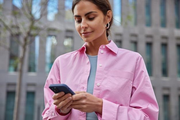 아름다운 밀레니엄 소녀의 수평 사진은 도시에서 휴대폰을 사용하여 경로를 찾기 위해 새로운 관심 장소를 탐색하며 흐릿한 건물에 분홍색 셔츠 포즈를 취합니다