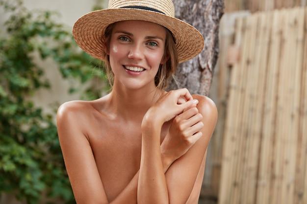 Горизонтальный снимок красивой улыбающейся женщины в соломенной шляпе, которая скрывает идеальное стройное тело, демонстрирует белые ровные зубы, приятно улыбается, проводит летние каникулы с любовником.