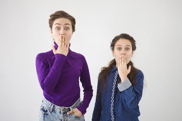 Горизонтальный снимок красивой стильной 20-летней женщины и ее сестры-подростка, выражающих удивление и полное недоверие, прикрывая рты