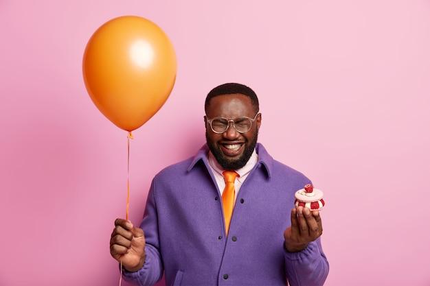 Горизонтальный снимок черного мужчины держит надутый воздушный шар, сливочный кекс, искренне смеется, поздравляет друга с выпускным, устраивает вечеринку